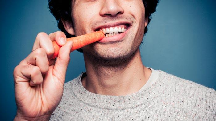 мужчина ест морковь